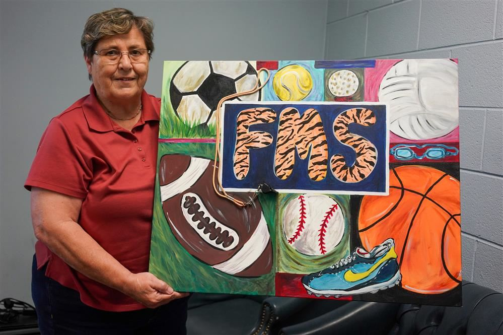 Sissy Parks is pictured holding a painting from her office
